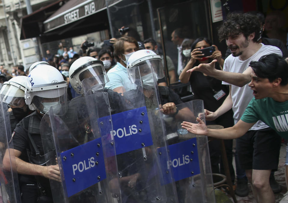 Activists, right, scream to police officers in riot gear moving to disperse the crowds that tried to stage a pride event in central Istanbul, Saturday, June 26, 2021. Police used tear gas and rubber bullets to disperse the crowds and detained dozens of LGTBI activists as hundreds defied a ban and tried to stage a gay pride event. (AP Photo/Emrah Gurel)