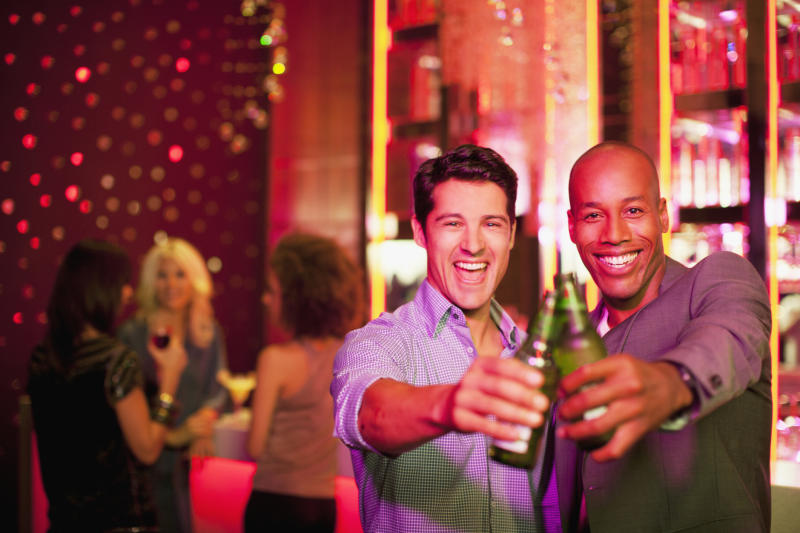 Two young men holding beers in a bar