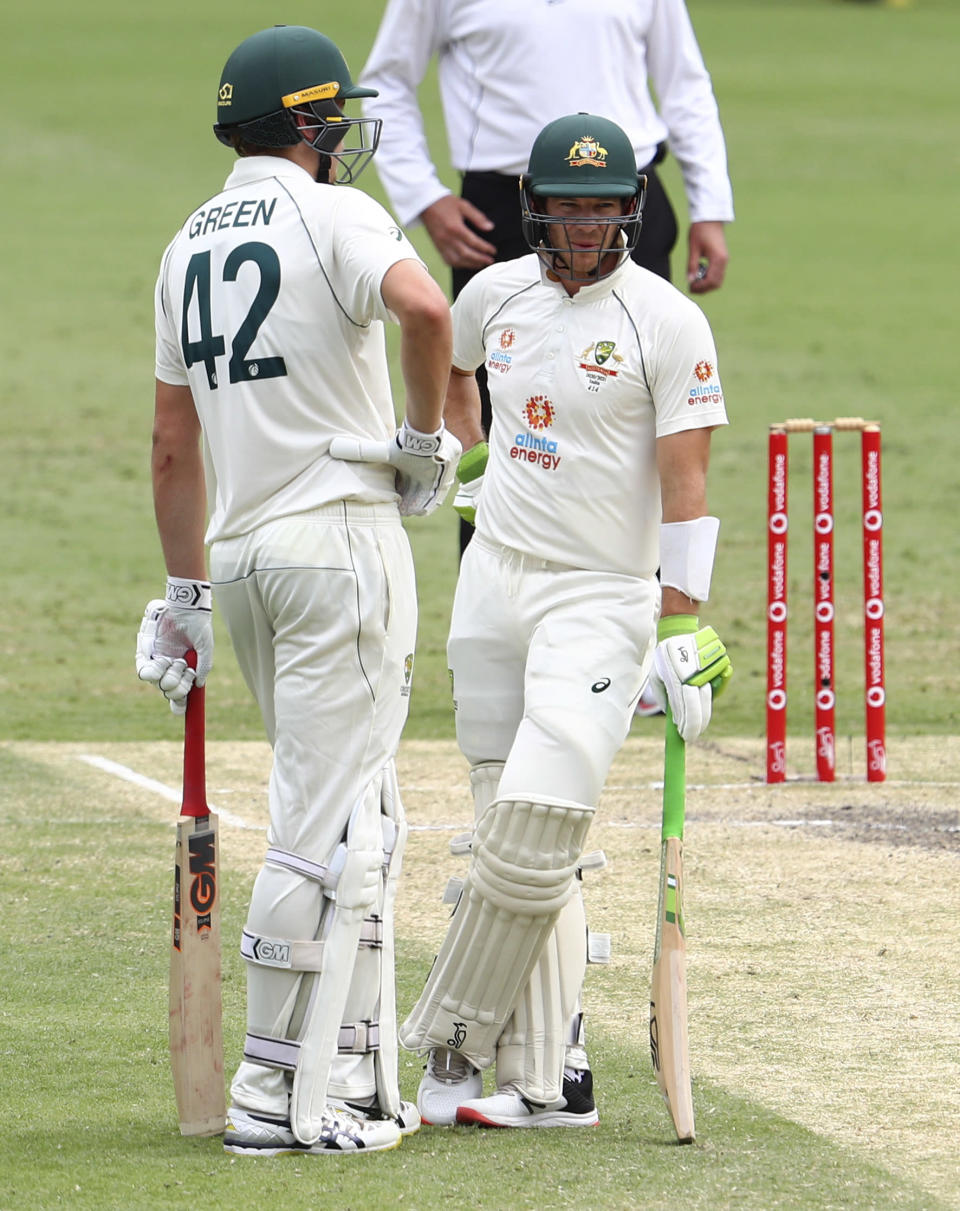 Australian captain Tim Paine talks with batting partner Cameron Green, left, during play on day four of the fourth cricket test between India and Australia at the Gabba, Brisbane, Australia, Monday, Jan. 18, 2021. (AP Photo/Tertius Pickard)