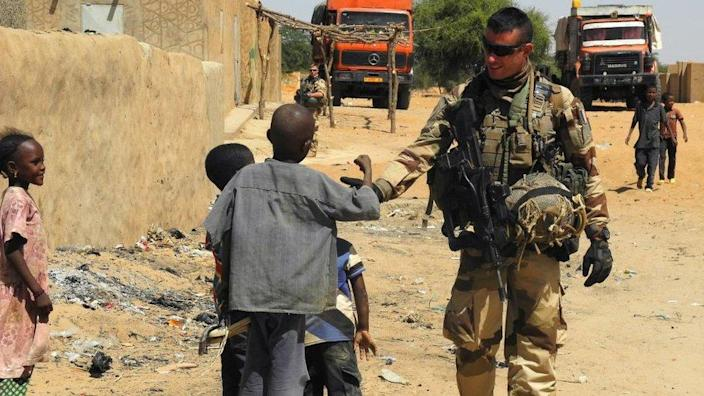 A soldier of France's Barkhane mission stands next to children as he patrols in In-Tillit on November 1, 2017 in Mali