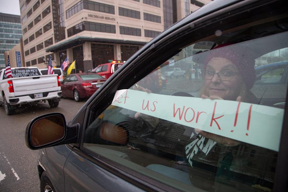 Kelly Dean a teacher from Lansing joins protesters as they block traffic around the Michigan State Capitol building in Lansing on April 15, 2020.