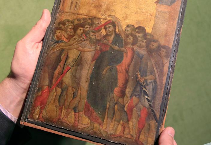 In this Tuesday, Sept. 24, 2019 file photo, art expert Stephane Pinta shows a 13th-century painting by Italian master Cimabue in Paris.