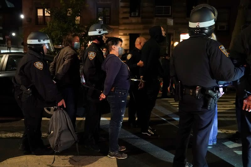 Police officers stand next to detained demonstrators near Washington Square park the day after Election Day in Manhattan, New York City