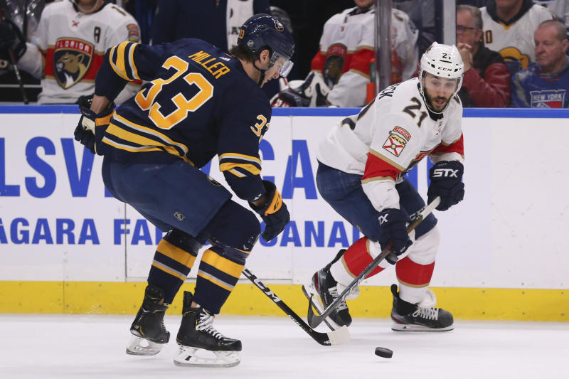 Buffalo Sabres defenseman Colin Miller (33) and Florida Panthers forward Vincent Trocheck (21) battle for the puck during the second period of an NHL hockey game Saturday, Jan. 4, 2020, in Buffalo, N.Y. (AP Photo/Jeffrey T. Barnes)