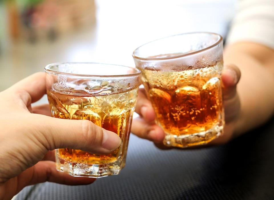 Men cheers with glasses of a whiskey soda alcohol cocktail drink
