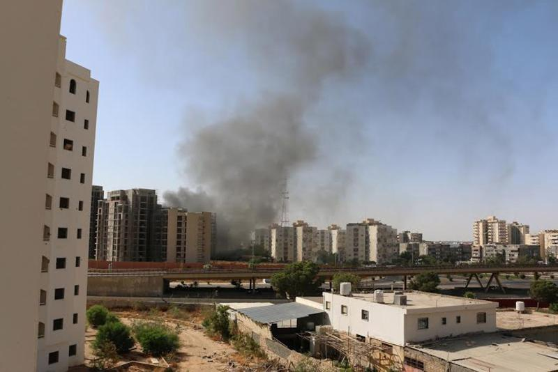 Smoke rises near buildings after heavy fighting between rival militias broke out near the airport in Tripoli July 13, 2014. Heavy fighting broke out between rival militias near the airport of the Libyan capital Tripoli on Sunday, residents and officials said, reporting explosions and gunfire that forced the suspension of all flights. REUTERS/ Hani Amara(LIBYA - Tags: POLITICS CIVIL UNREST)