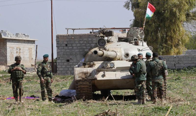 Kurdish peshmerga forces carry their weapons as they stand guard on the outskirts of Kirkuk