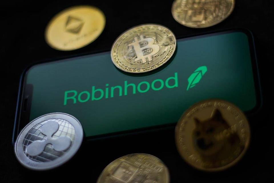 Robinhood logo displayed on a phone screen and representation of cryptocurrencies are seen in this illustration photo taken in Krakow, Poland on June 29, 2021 (Photo Illustration by Jakub Porzycki/NurPhoto via Getty Images)