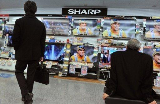 Customers look at Sharp televisions in a Tokyo store. The company is to slash 5,000 jobs by March, its first cuts since 1950 as it is hit by a prolonged slump in its key television and liquid crystal display sectors