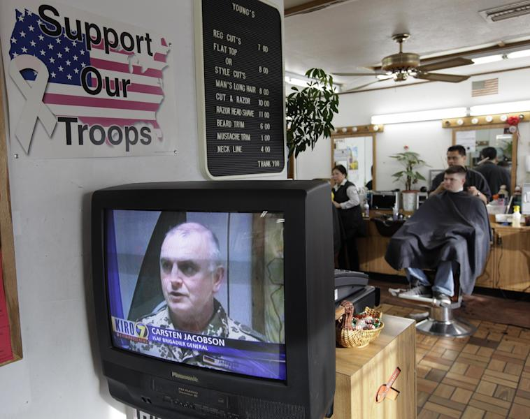 U.S. Army Spc. Jared Richardson, right, of Salt Lake City, gets his hair cut as he watches Brigadier General Carsten Jacobson, a spokesman for the International Security Assistance Force, on TV news near Joint Base Lewis McChord (JBLM), Sunday, March 11, 2012, in Lakewood, Wash. A U.S. Army sergeant from JBLM opened fire Sunday on Afghan villagers in Afghanistan as they slept, killing 16 people — mostly women and children — in an attack that reignited fury at the U.S. presence following a wave of deadly protests over Americans burning Qurans. (AP Photo/Ted S. Warren)