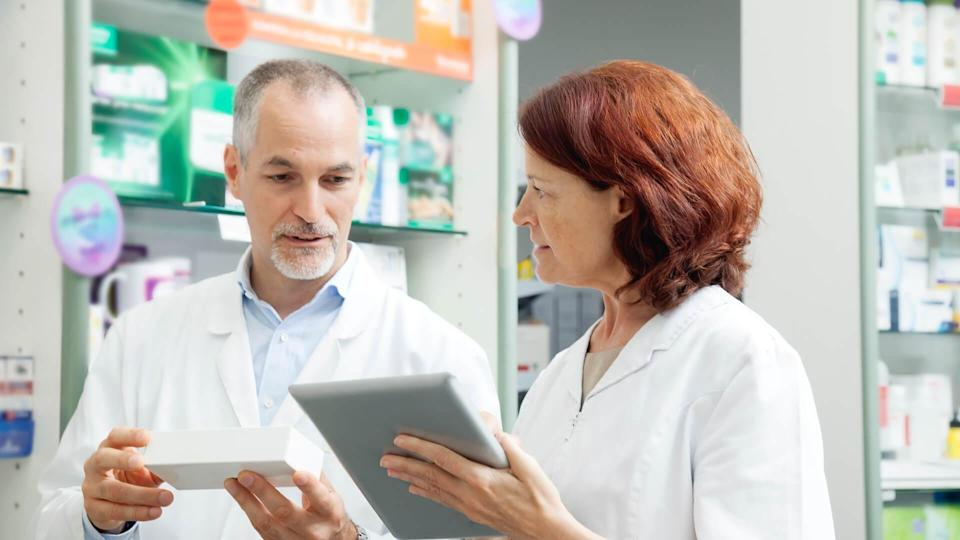 Two pharmacists, mature man and woman, working.