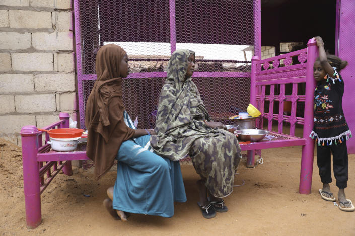 Saadia Ahmed, mother of the Sudanese migrant Mutawakel Ali, sits with her daughters at her home, in Khartoum, Sudan, Friday April 30, 2021. Ali narrowly missed drowning in Libya because he was late for the boat's departure. The rubber boat when on to sink at sea on approximately April 21, and its more than 100 passengers drowned. (AP Photo/Marwan Ali)