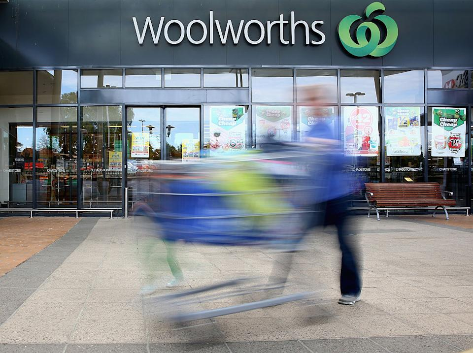 A shopper with a trolley rushes past a Woolworths supermarket.