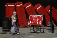 """FILE - In this Monday, June 22, 2020 file photo a sign requesting people stay two metres apart to try to reduce the spread of COVID-19 is displayed in front of """"Out of Order"""" a 1989 red phone box sculpture by British artist David Mach, in Kingston upon Thames, south west London. (AP Photo/Matt Dunham, File)"""
