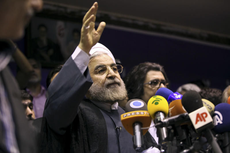 Iranian presidential candidate Hasan Rowhani waves to his supporters during a campaign rally in Tehran, Iran, Saturday, June 8, 2013. Rowhani, a candidate in next week's presidential elections, says he will reset Iran's economy and will reverse President Mahmoud Ahmadinejad's foreign policy directions if elected. (AP Photo/Ebrahim Noroozi)