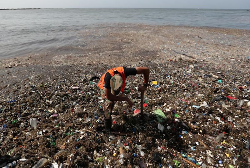 A soldier pauses while cleaning plastic and other debris on the shores of Montesinos beach, in Santo Domingo, Dominican Republic. (Photo: Ricardo Rojas/Reuters)