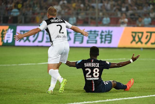 Paris Saint-Germain's Jean-Christophe Bahebeck (R) reacts after being brought down by Guingamp's Lars Jacobsen during the French season-opening Champions Trophy match in Beijing on August 2, 2014 (AFP Photo/Greg Baker)