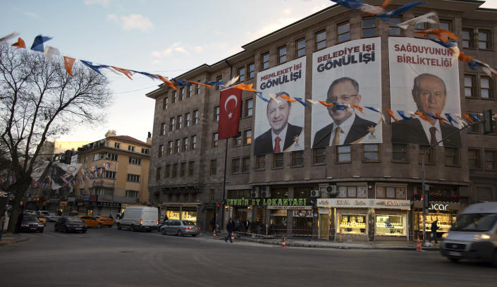 People walk in the old part of Turkish capital, Ankara, Turkey, Friday, March 29, 2019. A poster with images of Turkey's President Recep Tayyip Erdogan, left, Devlet Bahceli, leader of the opposition Nationalist Movement Party, MHP, right, and Mehmet Ozhaseki, the mayoral candidate for Ankara of Erdogan's ruling Justice and Development Party, AKP, and MHP is in the background, ahead of local elections scheduled for March 31, 2019. (AP Photo/Burhan Ozbilici)