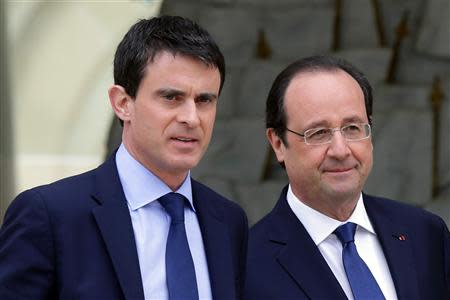 French President Hollande escorts newly-named Prime Minister Valls after the first cabinet meeting of the new government at the Elysee Palace in Paris