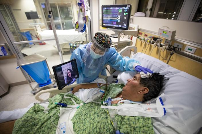 Registered Nurse Kat Yi holds an iPad up to Eduardo Rojas inside the ICU at Providence St. Jude Medical Center.