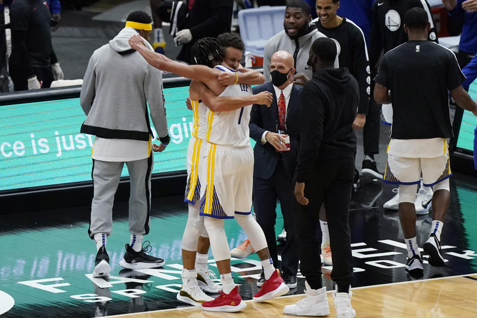 Golden State Warriors guard Stephen Curry, center left, celebrates with Damion Lee after the Warriors defeated the Chicago Bulls 129-128 in an NBA basketball game in Chicago, Sunday, Dec. 27, 2020. (AP Photo/Nam Y. Huh)