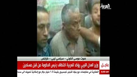 An undated still image aired by broadcaster Al Arabiya shows what it says is Libyan Prime Minister Ali Zeidan surrounded by men at an unidentified location. REUTERS/Al Arabiya via Reuters