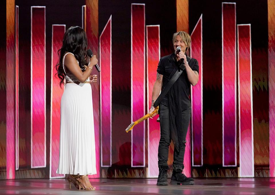 Award hosts Mickey Guyton, left, and Keith Urban shared some onstage banter after Urban performed.