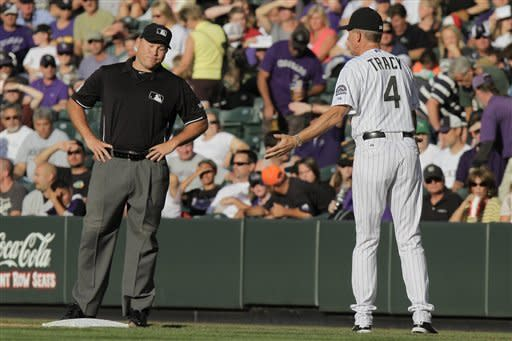 First base umpire Mark Carlson, left, reacts to a complaining Colorado Rockies manager Jim Tracy (4) during the first inning of a baseball game against the Washington Nationals, Wednesday, June 27, 2012, in Denver, Colo. (AP Photo/Barry Gutierrez)