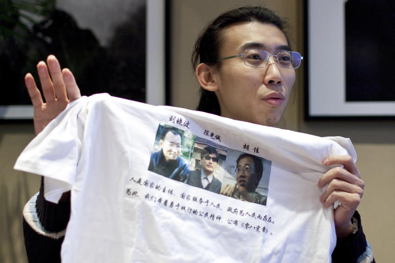 In this Monday, Dec. 6, 2010 photo, Wang Zhongxia shows a T-shirt he made to promote Charter 08, which shows photos of human rights activists Liu Xiaobo, left, Chen Guangcheng, center, and Hu Jia, right, and quotes from Charter 8 during an interview in Beijing, China. China has not been able to stop the news about imprisoned Nobel Peace Prize winner Liu Xiaobo from reaching a new generation of curious Chinese. (AP Photo/Alexander F. Yuan)