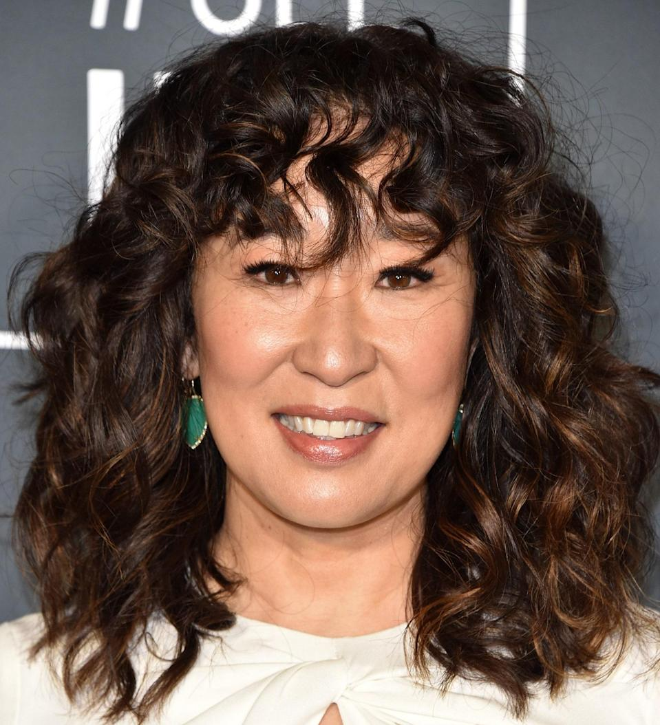 """While you might think bangs are only for straight hair, allow Sandra Oh to convince you otherwise. The secret to getting it right is working with someone who specializes in <a href=""""https://www.glamour.com/story/what-is-dry-cutting-haircut-technique?mbid=synd_yahoo_rss"""" rel=""""nofollow noopener"""" target=""""_blank"""" data-ylk=""""slk:dry cutting"""" class=""""link rapid-noclick-resp"""">dry cutting</a>. """"Because curls are unpredictable, a trained stylist will want to see what your curls are doing in their natural state,"""" celebrity hairstylist and Dove curl expert <a href=""""https://www.instagram.com/cynthiaglam/"""" rel=""""nofollow noopener"""" target=""""_blank"""" data-ylk=""""slk:Cynthia Alvarez"""" class=""""link rapid-noclick-resp"""">Cynthia Alvarez</a> says. """"This will help determine where they're going to fall, how to frame your face, and how to work with the different textures throughout your head."""""""
