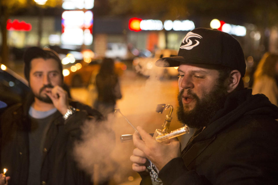 FILE - In this Oct. 17, 2018, file photo, people smoke cannabis on the street in Toronto. China has become the latest Asian country to warn its citizens in Canada about marijuana after it was legalized for recreational use there. (Chris Young/The Canadian Press via AP, File)