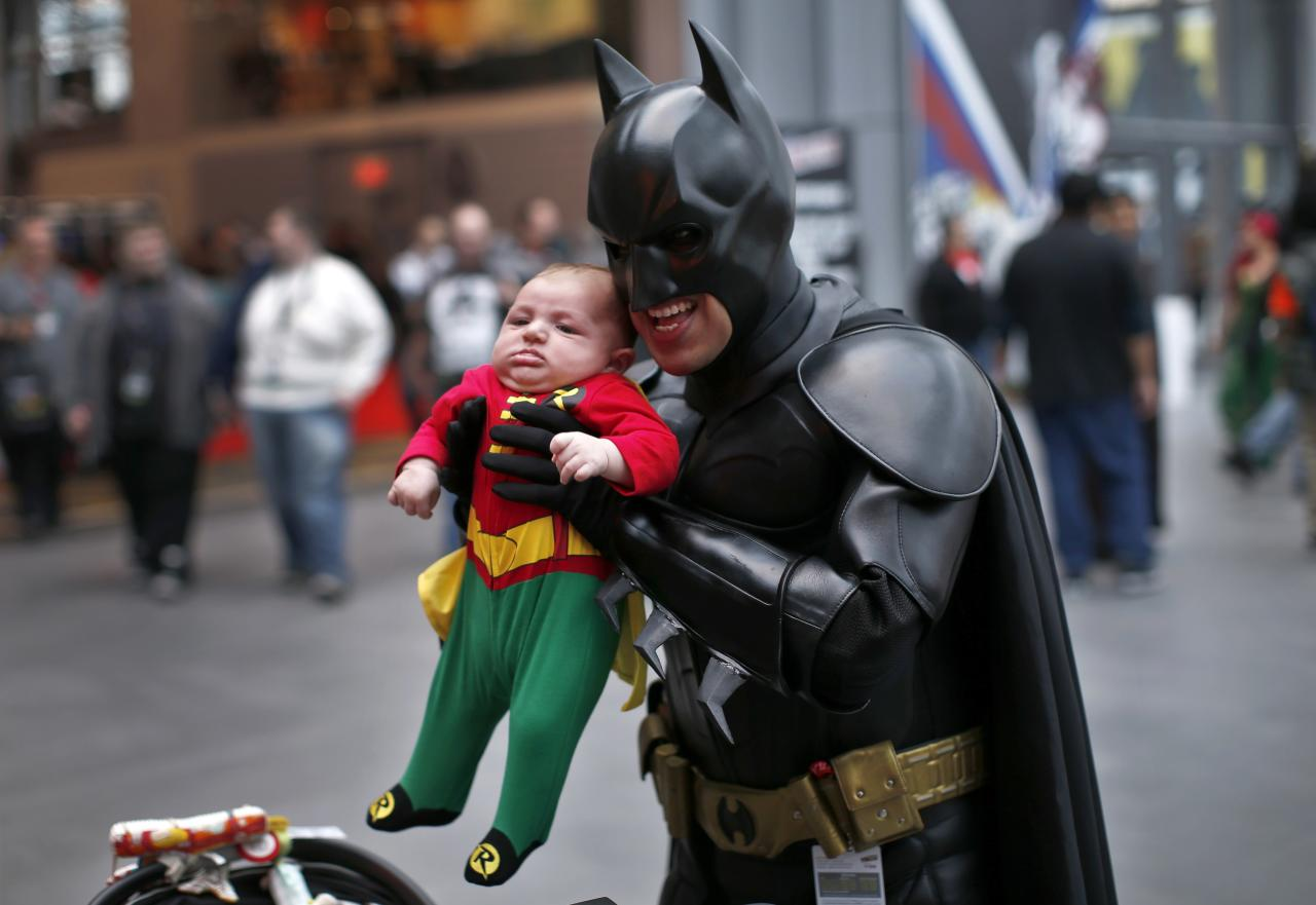 A man in a Batman costume holds up an infant dressed as Robin at New York's Comic-Con convention October 11, 2013. The event draws thousands of costumed fans, panels of pop culture luminaries and features a sprawling floor of vendors in a space equivalent to more than three football fields at the Jacob Javitz Convention Center on Manhattan's West side and has grown into one of the largest cons drawing an expected 120,000 fans. REUTERS/Mike Segar (UNITED STATES - Tags: ENTERTAINMENT SOCIETY)