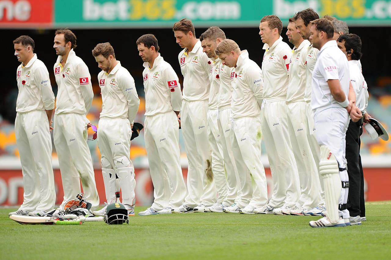 BRISBANE, AUSTRALIA - NOVEMBER 11:  The Australia team observe a minute silence to commemorate Remembrance Day during day three of the First Test match between Australia and South Africa at The Gabba on November 11, 2012 in Brisbane, Australia.  (Photo by Matt Roberts/Getty Images)
