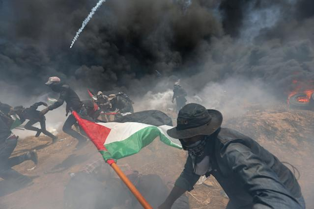 Palestinian demonstrators run for cover from Israeli fire and tear gas at the Israel-Gaza border during a protest against the U.S. Embassy's relocation to Jerusalem on May 14, 2018. (Photo: Ibraheem Abu Mustafa/Reuters)