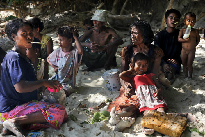 In this Sunday, Feb. 9, 2014 photo, a group of Moken families, nomads of the sea, rest in the shade of trees on Island 115 in Mergui Archipelago, Myanmar. The Moken group of several families are spending 10 days hunting for squid and whatever else they can collect before returning to their village on another island toward Myanmar's southwestern coast with a lacework of 800 islands, what is known as the Lost World. Isolated for decades by the country's former military regime and piracy, the Mergui archipelago is thought by scientists to harbor some of the world's most important marine biodiversity and looms as a lodestone for those eager to experience one of Asia's last tourism frontiers before, as many fear, it succumbs to the ravages that have befallen many of the continent's once pristine seascapes. (AP Photo/Altaf Qadri)