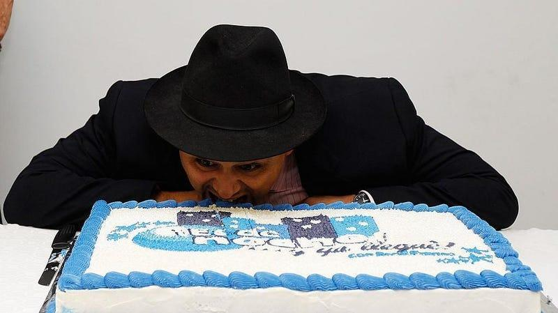 Man pretends to bite into large cake