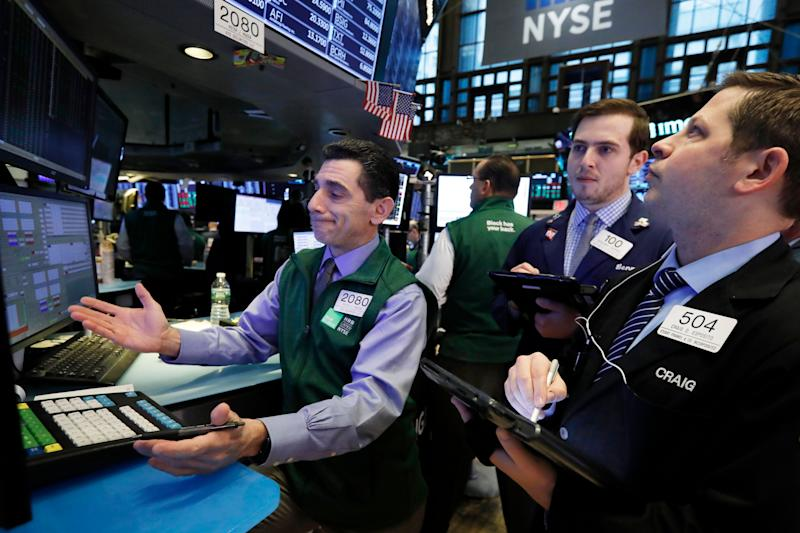 Specialist Peter Mazza, left, work with traders at his post on the floor of the New York Stock Exchange, Tuesday, Jan. 29, 2019. Stocks are opening slightly higher on Wall Street as several big U.S. companies reported solid results for the latest quarter. (AP Photo/Richard Drew)
