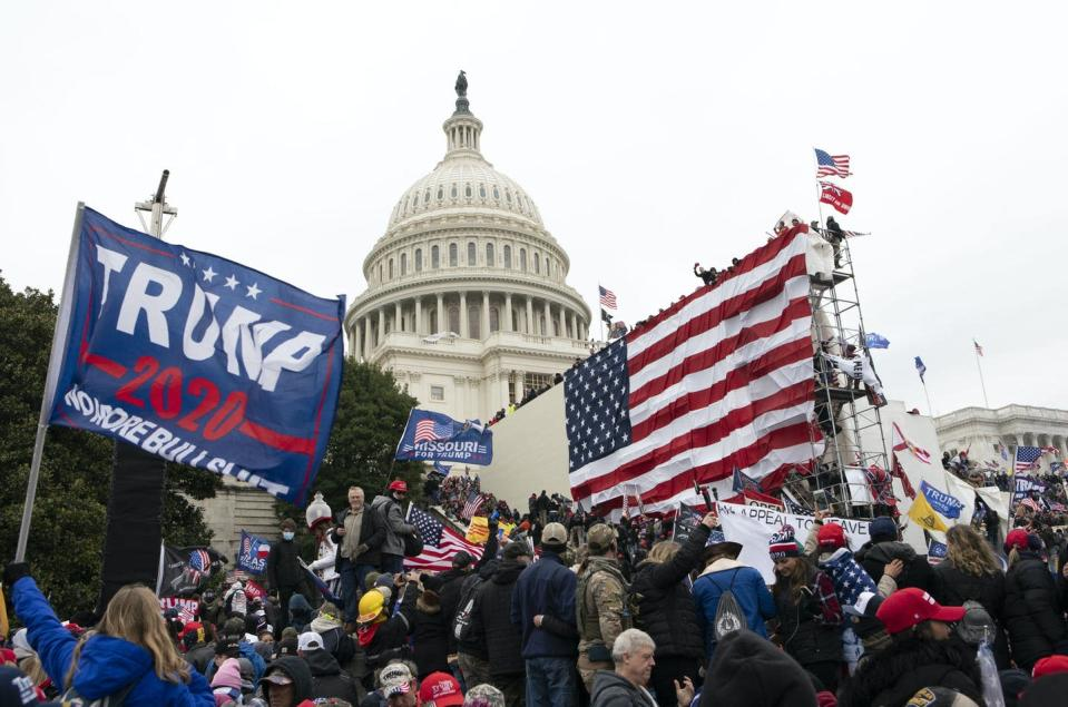 """<span class=""""caption"""">In this Jan. 6, 2021, photo, Donald Trump supporters gather outside the U.S. Capitol as protesters begin to raid the building.</span> <span class=""""attribution""""><span class=""""source"""">Protesters waving Trump signs stand outside the U.S. Capitol.</span></span>"""