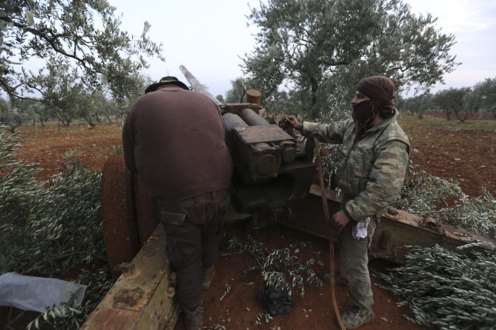 Syrian rebel fighters prepare to shoot a howitzer toward the government positions near the village of Nerab, in Idlib province, Thursday, Feb. 6, 2020. Turkey sent more reinforcements into northwestern Syria on Thursday, setting up new positions in an attempt to stop a Syrian government offensive on the last rebel stronghold in the war-torn country, state media and opposition activists said. (AP Photo/Ghaith Alsayed)