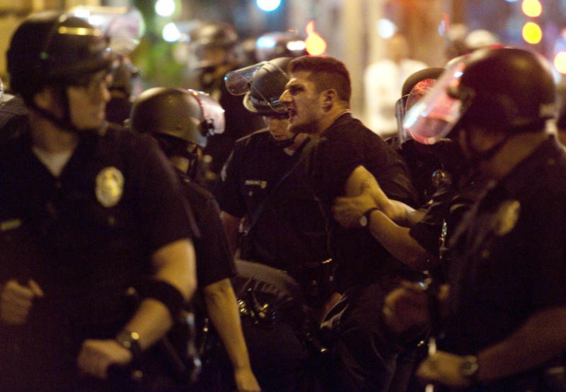 A unidentified man is arrested by Los Angeles police on Fourth Street and Spring Street in downtown Los Angeles late Thursday, July 12, 2012. An officer was injured as police in riot gear broke up a crowd of about 200 protesters who filled Los Angeles streets during downtown's monthly Art Walk. LAPD spokeswoman Karen Rayner says there have been several arrests, and at least one officer injured, but had no further details.    (AP Photo/Grant Hindsley)