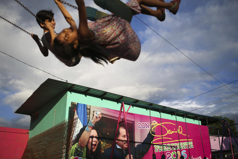 FILE - In this Nov. 4, 2016 file photo, children swing in a park next to an election billboard promoting Nicaragua's President Daniel Ortega and running mate, his wife Rosario Murillo in Managua, Nicaragua. Nicaraguan opposition leaders returned to the negotiating table Wednesday, July 31, 2019, at a business center where talks on resolving the country's political crisis stalled months ago, but there was nobody there to talk to. The opposition wants Ortega, 73, to negotiate electoral reform and early elections. (AP Photo/Esteban Felix, File)