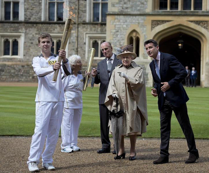 Britain's Queen Elizabeth II, second right, her husband Prince Philip, center, and London 2012 Chairman Sebastian Coe, right, watch after seventy four year-old Olympic torch bearer Gina Macgregor, second left, handed the Olympic Flame onto Phil Wells, left, andl Wells leaves carrying the Olympic flame at Windsor Castle, Windsor, England Tuesday July 10, 2012. The London 2012 Olympic Games will start on July 27, 2012. (AP Photo/Ben Stansall, Pool)