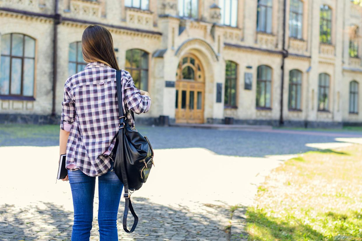 First day at university for young happy female student in casual clothes with backpack on her shoulders. View from back, she is looking at the entrance of the building