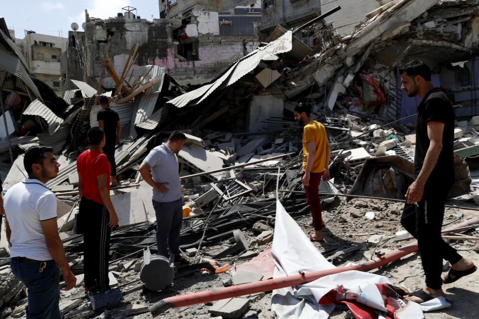 People inspect the rubble of destroyed residential building which was hit by Israeli airstrikes, in Gaza City, Thursday, May 20, 2021. (AP Photo/Adel Hana)