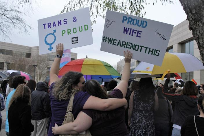 <p>Two people hold up signs protesting the passage of North Carolina legislation that limits the bathroom options for transgender people, during a rally that drew about 100 people to the Charlotte-Mecklenburg Government Center in Charlotte, N.C., on March 31, 2016.<i> (Skip Foreman/AP)</i></p>