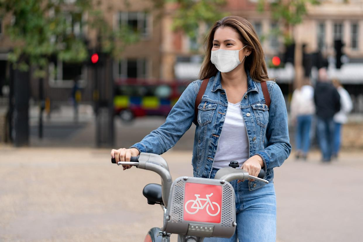 Portrait of a happy woman outdoors wearing a facemask to avoid the spread of coronavirus and renting a bike in London – pandemic lifestyle concepts