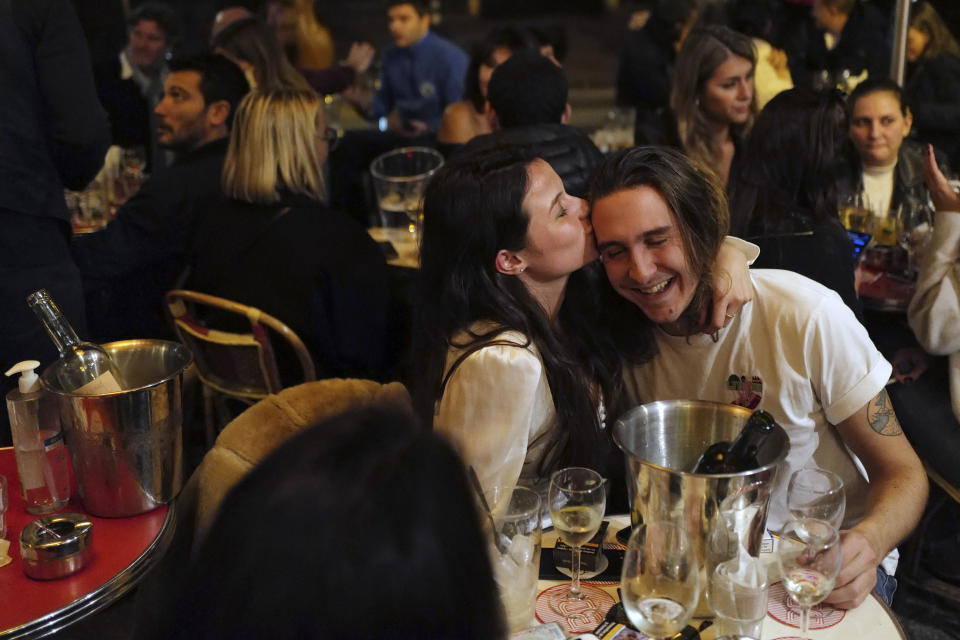 A couple kiss during a drink on the terrace of a restaurant before the nightly curfew due to the restrictions against the spread of coronavirus, in Paris, France, Friday, Oct. 23, 2020. In much of Europe, city squares and streets, be they wide, elegant boulevards like in Paris or cobblestoned alleys in Rome, serve as animated evening extensions of drawing rooms and living rooms. As Coronavirus restrictions once again put limitations on how we live and socialize, AP photographers across Europe delivered a snapshot of how Friday evening, the gateway to the weekend, looks and feels. (AP Photo/Francois Mori)