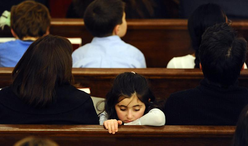 A child sits with her family in a pew during an interfaith a sermon at Newtown Congregational Church in Newtown, Conn., Sunday, Jan. 20, 2013. The Rev. James A. Forbes, Jr., who led one of the country's most prominent liberal Protestant churches, is speaking at the church to honor the victims of last month's school shooting and the legacy of the Rev. Martin Luther King Jr. (AP Photo/Jessica Hill)