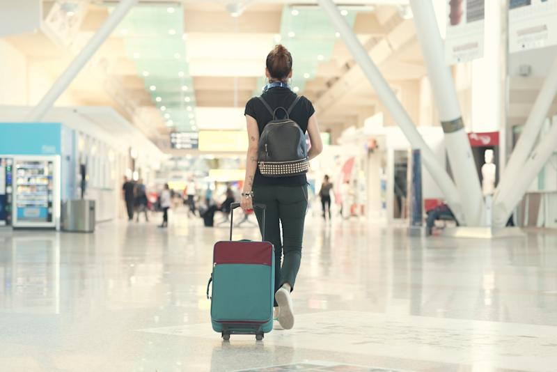 Back view of woman pulling her luggage strolling inside the airport terminal