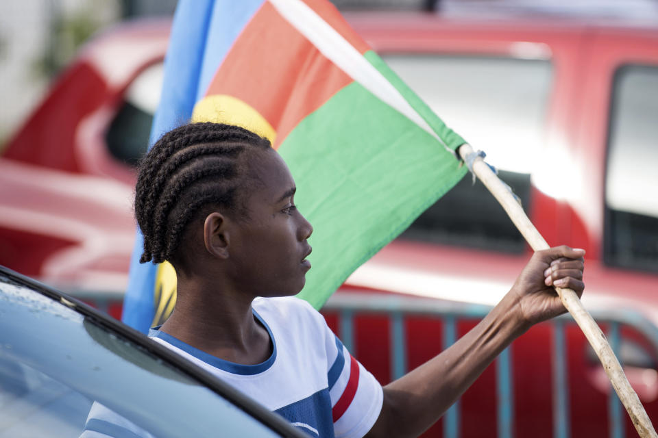 An Independence supporter holds the Kanak flag outside a voting station in the Riviere Salee district of Noumea, New Caledonia, Sunday, Oct.4, 2020. Voters in New Caledonia, a French archipelago in the South Pacific, were deciding Sunday whether they want independence from France in a referendum that marks a milestone in a three-decade decolonization effort. If voters choose independence, a transition period will immediately open so that the archipelago can get ready for its future status. Otherwise, New Caledonia will remain a French territory. (AP Photo/Mathurin Derel)
